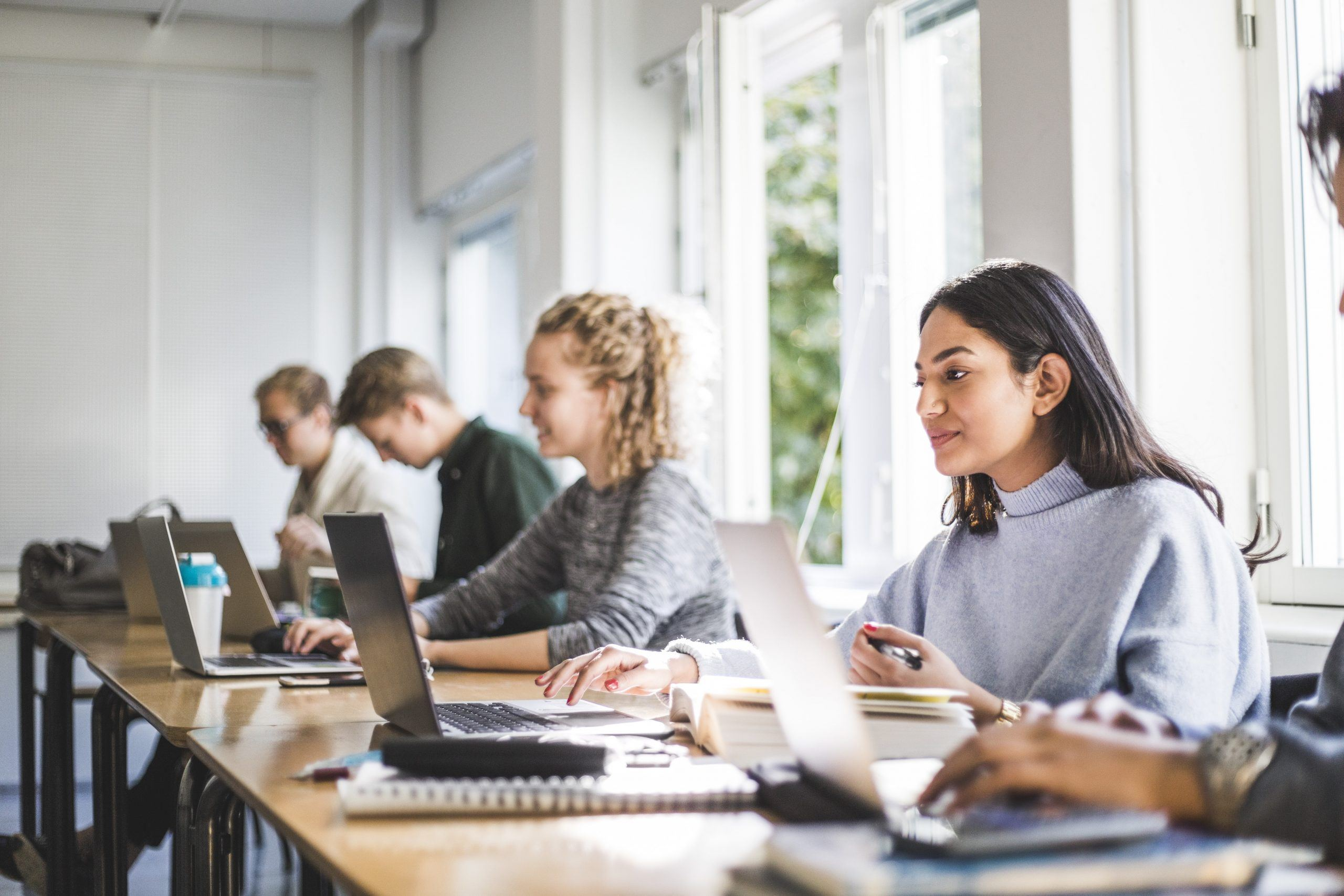 Male and female students using laptops in classroom